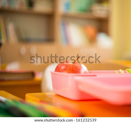 Food container with apple and salad in classroom  - stock photo