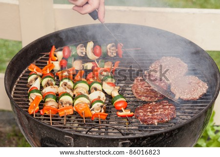 Food cooking on a charcoal grill in a park. - stock photo