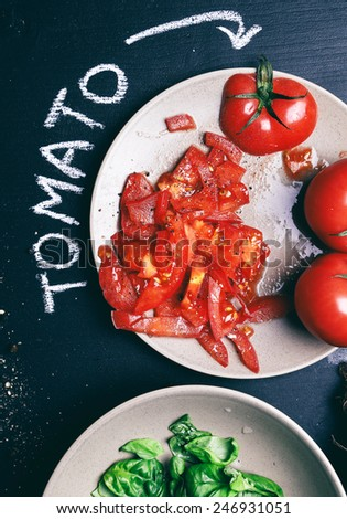 Food, cooking. Salad with basil and tomato on the table - stock photo