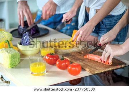 Food cooking together. Close-up view of the hands of young smiling loving couple cook dinner or breakfast in the kitchen while cut fruits and vegetables in the kitchen in the apartment