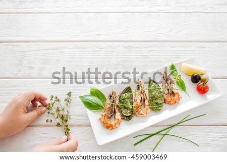 Food decoration, white wooden background, free space. Seafood meal with grilled shrimps and stuffed mussels - stock photo
