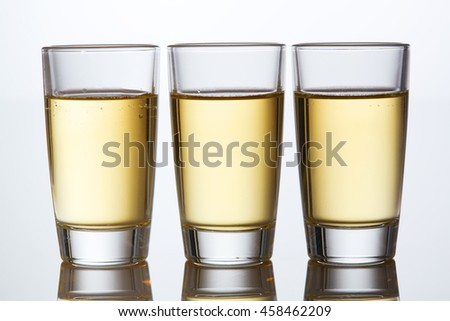 Food & drink alcohol drinks party concept: A set of shots of alcohol drinks. Set of tequila glasses with yellow beverage on a white background with reflection. Closeup.