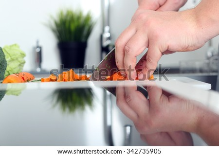 food, family, cooking and people concept - Man chopping a carrot on cutting board with knife in kitchen  - stock photo