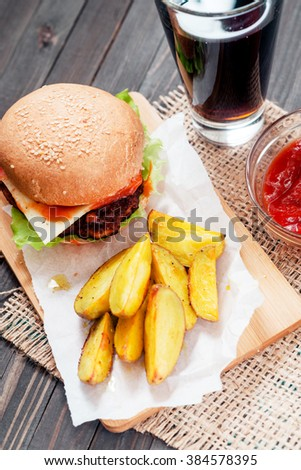 food, fast food, burgers with cheese , meat patty , lettuce, sauce , Baked potatoes and a drink , cola or beer on a wooden background