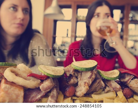 Food feast with focus on food. Vintage style image with blurred woman drinking beer. - stock photo
