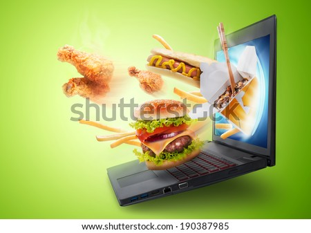 Food flying out of a laptop screen - stock photo