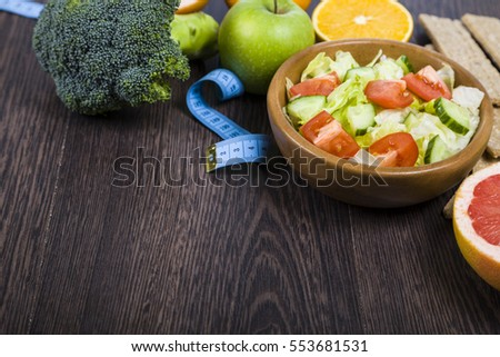 Food for diet and measuring tape on a dark wooden table. Concept of diet and healthy lifestyle.