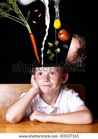 Food for thought.  Happy school child sitting at desk while his head is being filled with nutritious foods. - stock photo