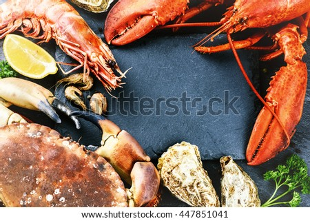 Food frame with crustacean for dinner. Lobster, crab, jumbo shrimps and oysters on dark background