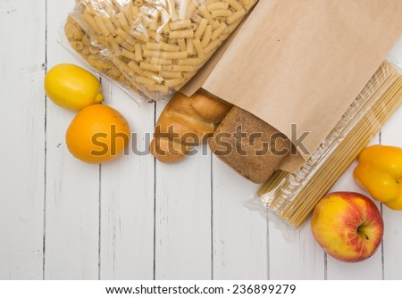 Food from supermarket in a paper craft bag on a white wooden background. Fruits, vegetables, bread, pasta - stock photo
