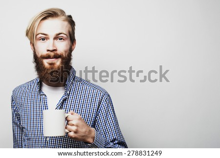 food, happiness and people concept: young bearded man with a cup of coffee against grey background - stock photo