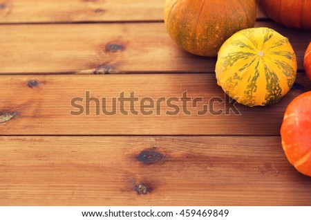 food, harvest, season and autumn concept - close up of pumpkins on wooden table at home - stock photo