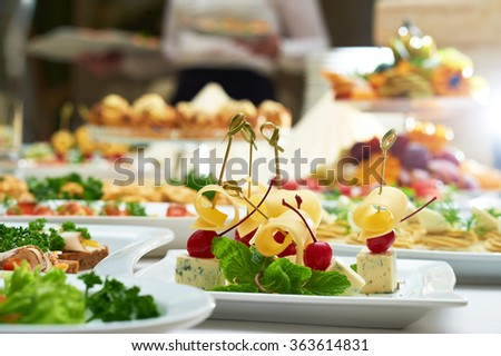 Food heaven. Selective focus on a cheese plate on the restaurant table full of delicious snacks and appetizers - stock photo