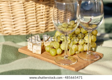 food, holidays, celebration and summer concept - picnic basket with wine glasses, grapes and cheese on wooden board