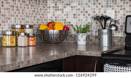 Food ingredients and green herbs on modern kitchen countertop. - stock photo