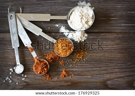 Food ingredients and kitchen utensils for cooking on a wooden board. Measuring spoons with cocoa, flour and brown sugar.  - stock photo