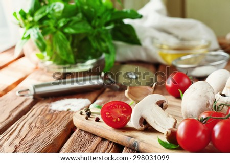 Food ingredients for pizza or pasta dishes. Fresh cherry tomatoes, mushrooms, garlic, basil leaves, olive oil. Close-up. Copy space. Free space for text - stock photo