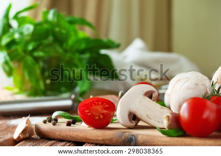 Food ingredients for pizza or pasta dishes. Fresh cherry tomatoes, mushrooms, garlic, basil leaves. Close-up. Copy space. Free space for text. From the eye level - stock photo