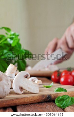 Food ingredients for pizza or pasta dishes on the cutting board. Fresh cherry tomatoes, mushrooms, basil leaves. In the background a men hand chopped mushrooms. Closeup.Copy space. Free space for text - stock photo