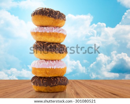 food, junk-food and eating concept - close up of glazed donuts pile on wooden table over blue sky and clouds background - stock photo