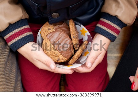 food, junk-food, culinary, baking and eating concept - close up of chocolate oatmeal cookies on plate in hands of child