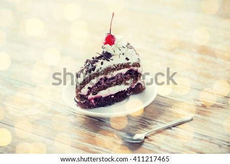 food, junk-food, culinary, baking and holidays concept - piece of delicious cherry chocolate layer cake on saucer with spoon on wooden table over holidays lights background - stock photo