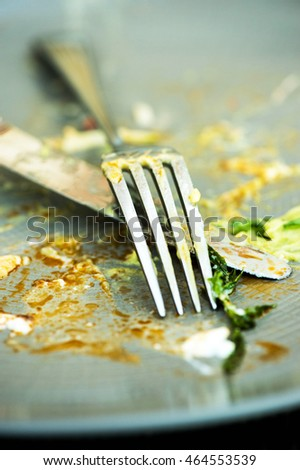 Food Left Overs on a Plate With a Knife and Fork After Finishing a Meal