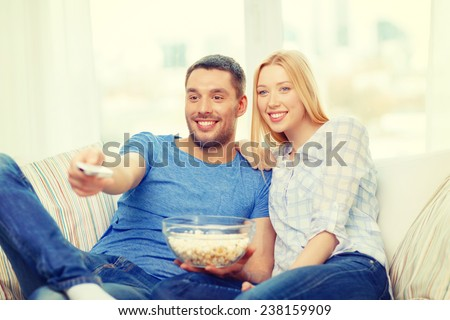 food, love, family and happiness concept - smiling couple with popcorn watching movie at home - stock photo