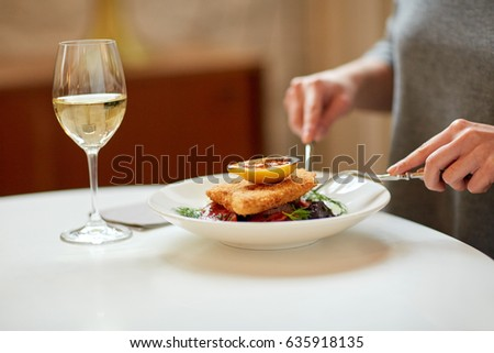 food, new nordic cuisine and people concept - woman eating breaded fish fillet with oven-baked beetroot and tomato salad with fork and knife at cafe or restaurant