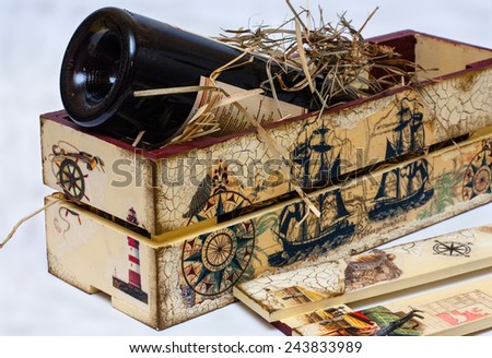 Food, objects. Bottle of red wine in a box for wine with hay. - stock photo