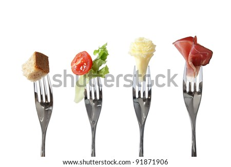 Food on forks: bread, vegetable, cheese and meat - four basic nutrition - stock photo