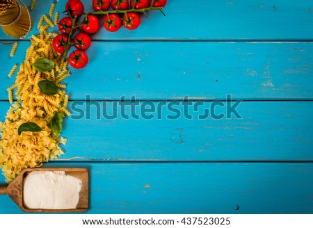 Food or cooking backgroud with pasta, tomato, spaghetti, penne, basil and flour on blue wood table.Top view. Copy space. - stock photo