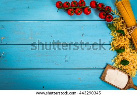Food or cooking background with pasta, tomato, spaghetti, penne, basil and flour on blue wood table.Top view.Copy space. - stock photo