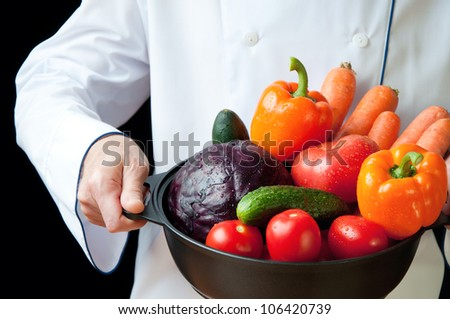 Food preparation: chef holding a frying pan with freshly gathered vegetables - stock photo