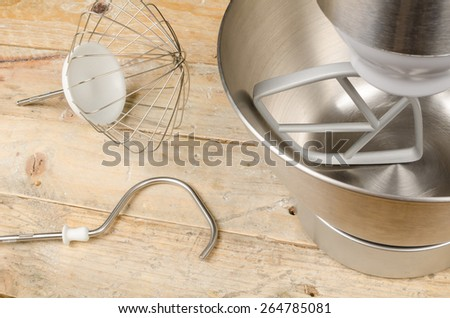 Food processor with different accessories on a rustic kitchen table - stock photo