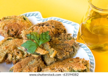Food Recipes - First courses - Italian fried artichokes and jar with olive oil isolated on yellow background.