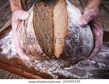food. rye bread in male hands - stock photo