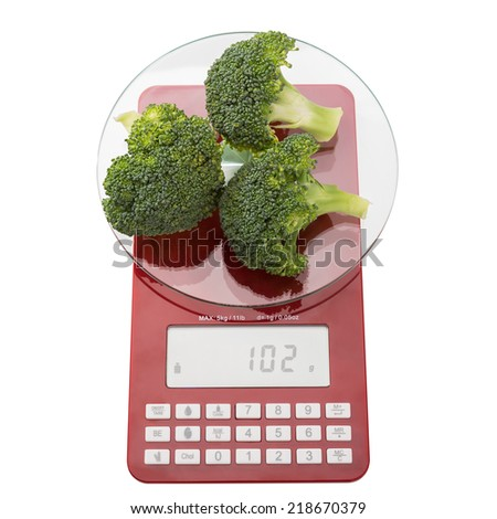 Food scales and green fresh broccoli. On a white background. - stock photo