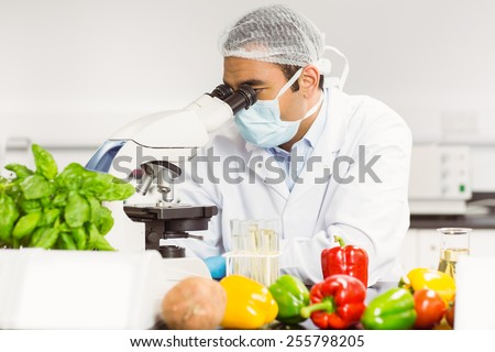 Food scientist using the microscope at the university - stock photo