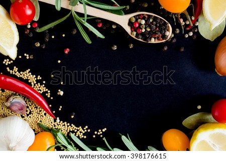 Food spice seasoning ingredients and vegetables for cooking in cuisine on dark background in the wooden spoon. Dry powder curry, ginger, chili, laurel and tomato, garlic, onion - stock photo