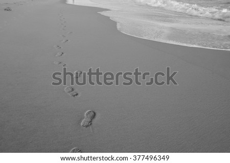 Food steps on the beach on black and white with the sand and the wave. slightly soft due to long exposure. - stock photo