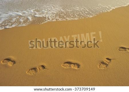 """Food steps on the beach with the effect of morning sun light on the sand and the wave with the word """" holiday time """" . slightly soft due to long exposure. - stock photo"""