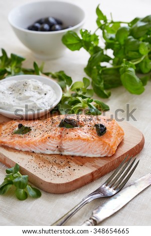 food still life photography of salmon fillet, Tartar sauce on a cutting board and basil leaves - stock photo