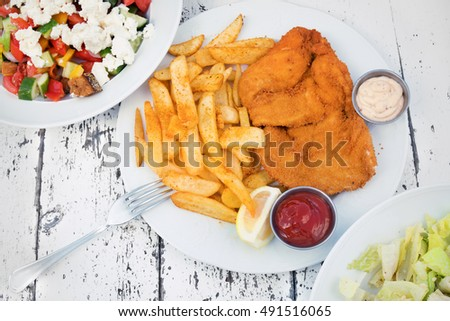 Food with potatoes and chicken schnitzel on textural wooden table with plates and salads at the edges
