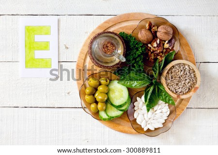 Foods containing vitamin E: walnuts, sunflower seeds, sunflower oil, herbs, pumpkin seeds, olives, cucumbers - stock photo