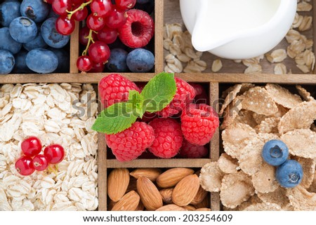 foods for breakfast - oatmeal, granola, nuts, berries and milk in wooden box, top view, horizontal, close-up - stock photo