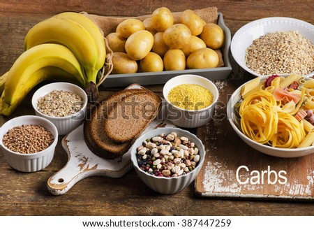 Foods high in carbohydrate on a rustic wooden background. Top view - stock photo