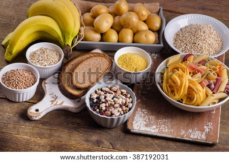 Foods high in carbohydrate on rustic wooden background. Top view - stock photo