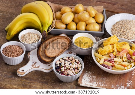 Foods high in carbohydrate on wooden table. Top view - stock photo