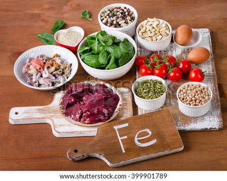 Foods high in Iron, including eggs, nuts, spinach, beans, seafood, liver, chickpeas. - stock photo